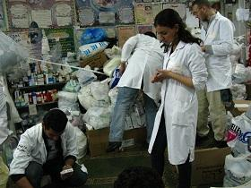Medical students sort through bags of donated medications to stock the pharmacy.