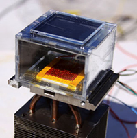 The proof-of-concept water harvester consists of an MOF layer under a glass plate, a condenser (the yellow square), and a heat sink extending below.